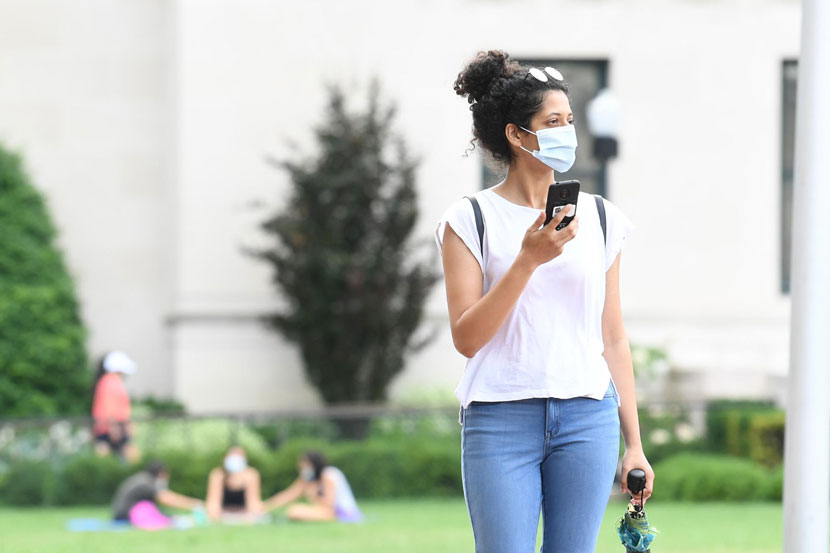 A student crosses the Columbia University campus wearing a face mask